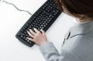 キーボードを打つ女性の画像